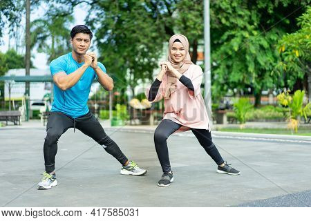 Muslim Couples In Gym Clothes Doing The Leg Warm-up Movement Together Before Exercising