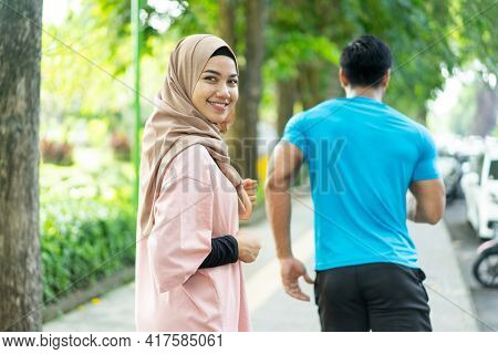 A Girl In A Veil Smile Looking At The Camera When Doing Jogging Together When Outdoor Exercise