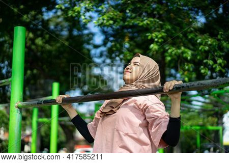 A Girl In A Veil Does Pull Ups To Work Out Her Hand Muscles