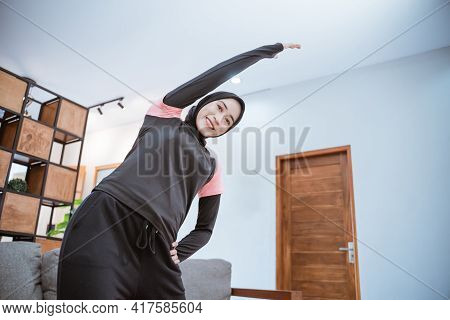 A Young Woman In A Hijab Sportswear Smiles While Warming Up With Her Body Leaning To The Side With O