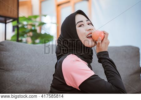 Close Up Of An Asian Woman In A Veil Sportswear While Holding And Bite An Apple While Sitting On The