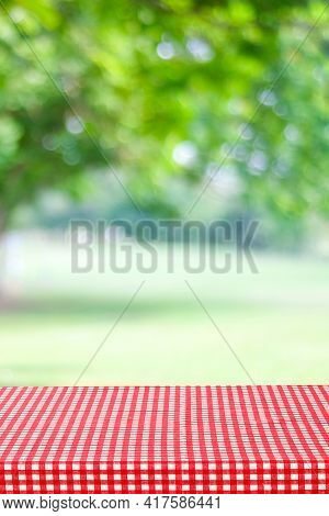 Empty Table With Red And White Tablecloth Over Blurred Park Nature Background, For Product Display M
