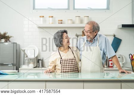 Couple Senior Asian Elder Happy Living In Home Kitchen. Grandfather Hug Grandmother With Happiness A
