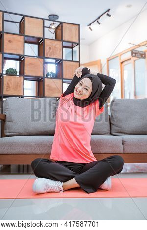 A Girl In A Veil Gym Outfit Smiles While Doing Hand Stretches While Sitting On The Floor With A Mat