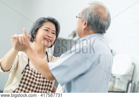 Couple Senior Asian Elder Happy Living In Home Kitchen. Grandfather And Grandmother Dance With Happi