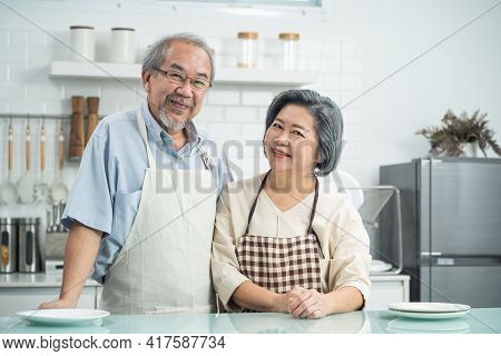 Couple Senior Asian Elderly Happy Living In Home Kitchen. Grandfather Hug Grandmother With Happiness
