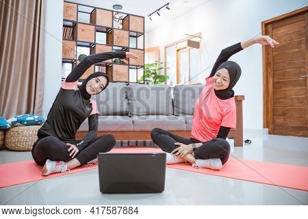 Two Women Wearing Hijab Sportswear Sit Cross-legged On The Floor With Their Bodies Leaning To The Si