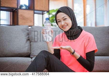 Asian Girl In A Veil Sportswear Smiles While Holding A Drinking Bottle With Hand Gestures Offer Some