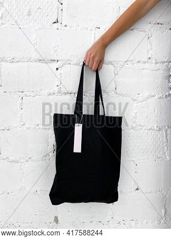 Womans Hand Holding A New Black Tote Bag Or Shopper With Blank Label