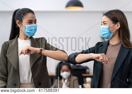 Two Colleague Female Workers In Office Company Have A Greeting By Touching The Elbow Or Elbow Bump T
