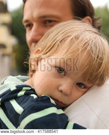 Child on father's shoulder outdoors