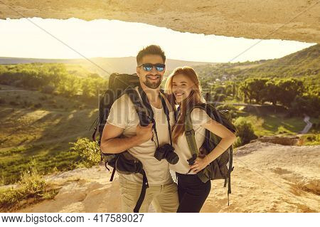 Happy Young Couple Of Hikers Standing In Mountains Cave At Sunset. Tourists Mountaineering On Summer