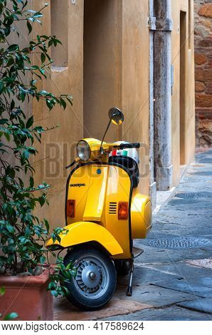 Pienza, Italy - October 13, 2017: Orange Vespa Parked On Old Cozy Street In Italy. Vespa On Narrow O