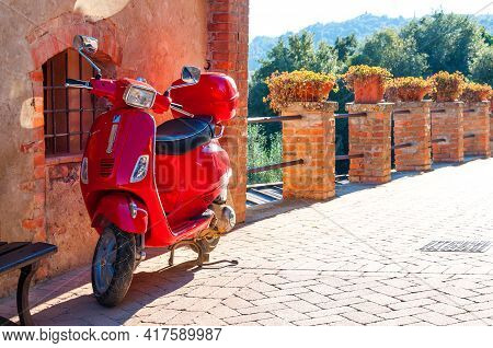 Pienza, Italy - October 16, 2017: Red Vespa Parked On Old Cozy Street In Italy. Vespa On Narrow Old