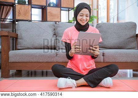 A Girl In A Veil Gym Outfit With A Smile Looking At A Tablet After Indoor Exercise
