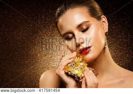 Beautiful Woman Holding Gold Jewelry In Hands. Model Face Golden Make Up. Skin Care. Closed Eyes. Be