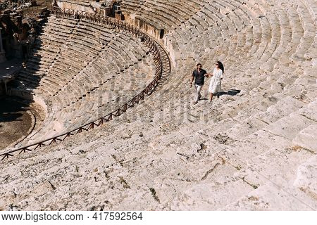 A Couple Runs Down The Stairs Of The Pamukkale Amphitheater In Turkey. A Man And A Woman Are Traveli