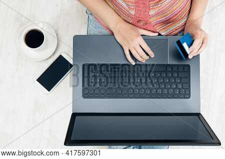 Woman Hand Holding Credit Card And Using Laptop Making Online Payment. Top View Of Hands Work With C