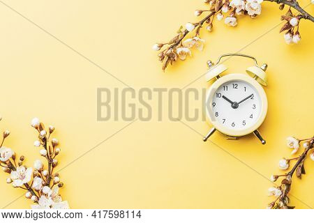 Spring Time Background. May Flowers And April Floral Nature With Alarm Clock On Yellow. Branches Of