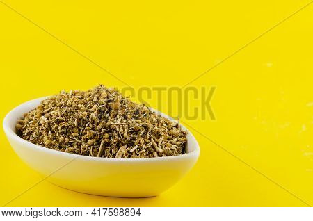 A Mixture Of Dried Medicinal Herbs In A White Ceramic Bowl On A Yellow Background. Crushed Various M