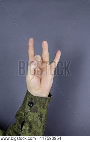 Hand In Camouflage Shows Gesture With His Fingers On Gray Background. Index, Ring Finger And Little