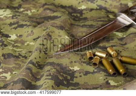 A Knife Blade And Some Random Casings On Camouflage Fabric. Knife Without Sheath And Group Of Pistol