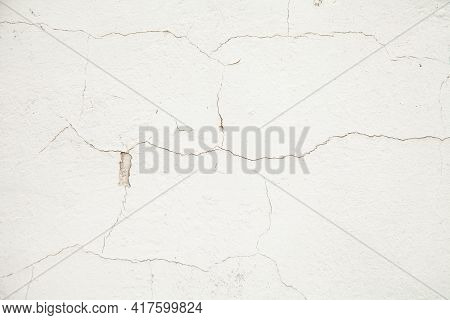 White Wall With Cracks. Cracks Texture On A White Abstract Background. Cracked Plaster On The Wall