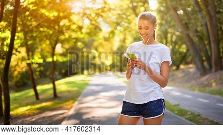 Woman Listen Music Earphones Before Jogging Summer Park Caucasian Female Preparing To Run Sunny Morn