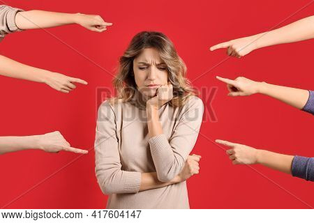 Stressed Woman Feeling Uncomfortable Because Of People Pointing At Her Against Red Background. Socia