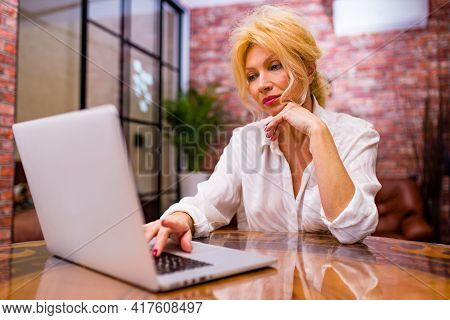 Mature Lady Sitting With Laptop In Living Room At Evening Light