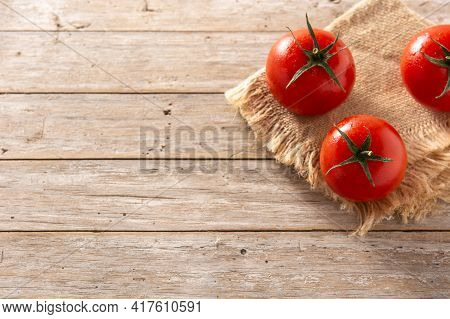 Organic Fresh Tomatoes On Rustic Wooden Table. Top View. Copy Space