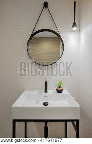 Interior Of Modern Style Bathroom In Refurbished Apartment. White Sink With Black Faucet And Round M