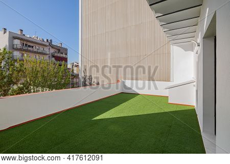Empty Sunny Terrace Of Refurbished Apartment With Artificial Green Grass Lawn. View To The Street An