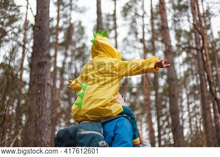 Mom And Child Walking In The Forest After The Rain In Raincoats Together, The Child Is Sitting On Th