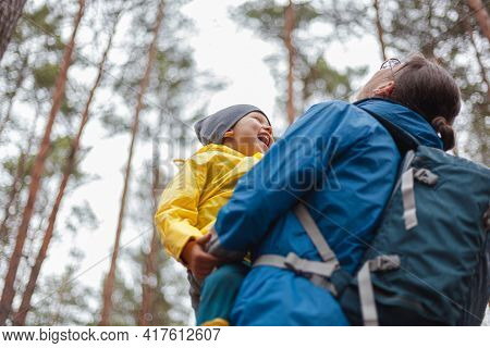 Happy Family Mom And Child Walk In The Forest After The Rain In Raincoats Together, Hug And Look At