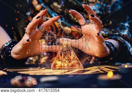 A Witch Conjures A Magic Glass Pyramid. Hands Close-up. Sparks Flare Up Near The Pyramid. The Concep