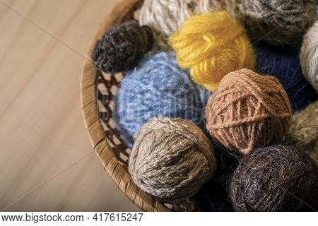 Knitting Supplies Close-up. Balls Of Knitting Wool In A Round Wicker Basket.
