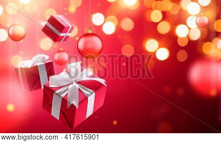 Christmas Gifts With Hanging Bauble Over Blurred Bokeh Light Background