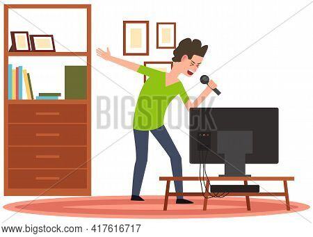 Man Holding Microphone And Singing In Karaoke To Music. Boy Stands With Mike Next To Tv At Home