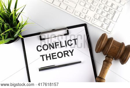 White Office Desk Table With Blank Sheet , Text Conflict Theory , Keyboard And Gavel,