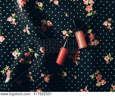 Pink Lipstick And Pink Glitter Lip Gloss On Floral Fabric Textural Background