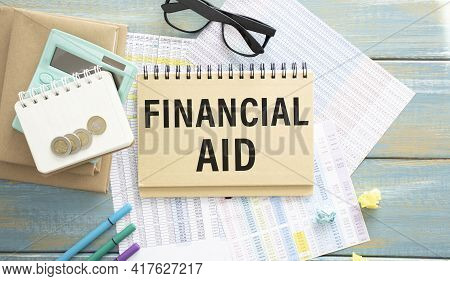 Financial Aid Text Written On A Notebook With Pencil, Calculator And Coins