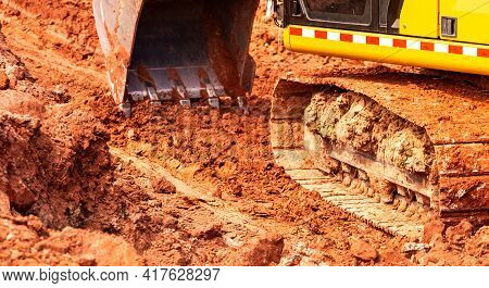 Selective Focus Backhoe Working By Digging Soil At Construction Site. Bucket Of Backhoe Digging Soil
