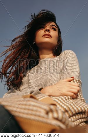 From Below Of Young Pensive Frustrated Brunette With Long Hair Dressed In Warm Knitwear Embracing He