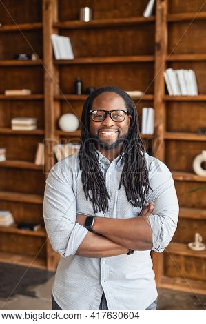 Vertical Portrait Of Smiling Young Handsome African American Man With Dreadlocks And Glasses Standin