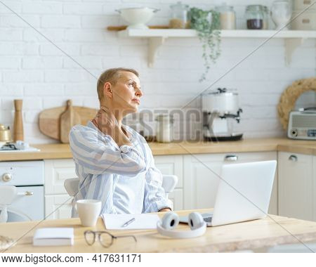 Need Some Rest. Tired Mature Woman Massaging Her Neck While Working Or Studying On Laptop Online At