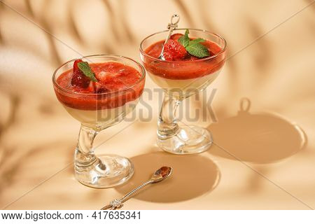 Two Glasses Of Traditional Italian Creamy Pudding Dessert Panna Cotta With Peppermint, Strawberry Ja