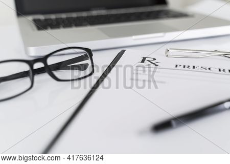 Rx Prescription, Laptop And Glasses On Pharmacy Work Table.