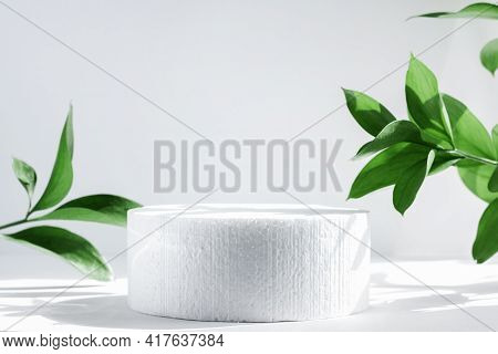Cylindrical Podium On A White Background With Hard Shadows And Leaves. Minimal Empty Scene Of Cosmet