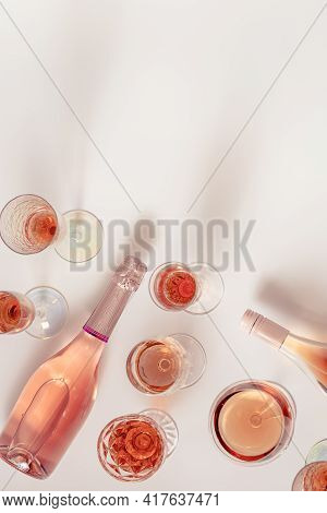 Many Glasses Of Rose Wine And Bottle Sparkling Pink Wine Top View. Light Alcohol Drink For Party.